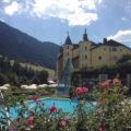 Blick auf Pool, Garten und Fassade Adler Dolomiti Spa Hotel