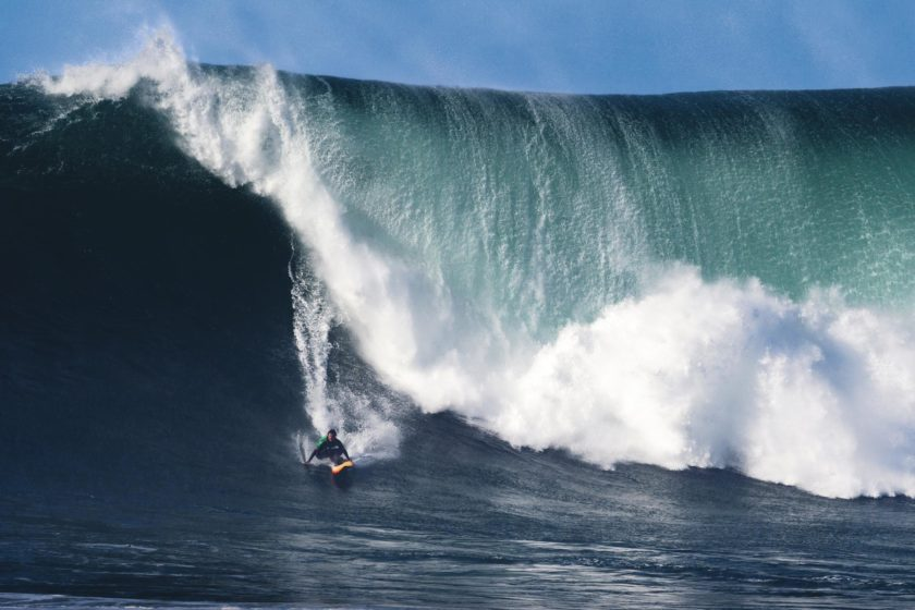 Surfer und Big Wave in Nazaré